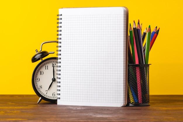 Wecker und notizblock auf dem schreibtisch