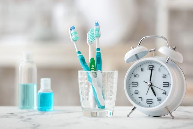 Wecker und satz mundpflegeprodukte auf dem tisch