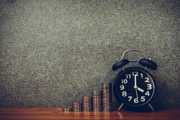 Wecker und schritt von münzenstapeln auf arbeitstisch, zeit für einsparungsgeldkonzept.