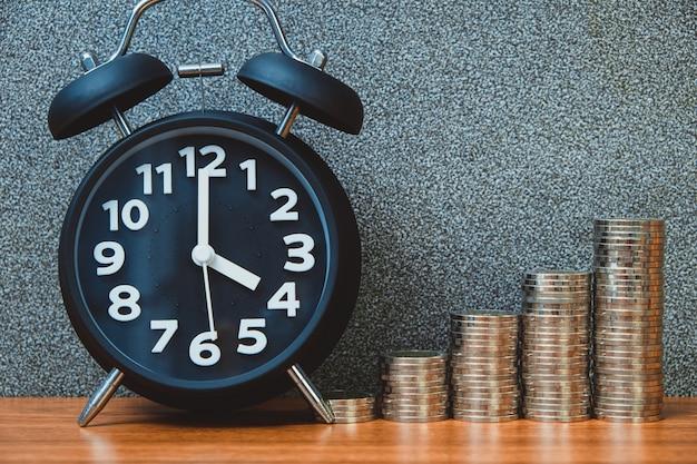 Wecker und schritt von münzenstapeln auf funktionstabelle, zeit für einsparungensgeldkonzept.