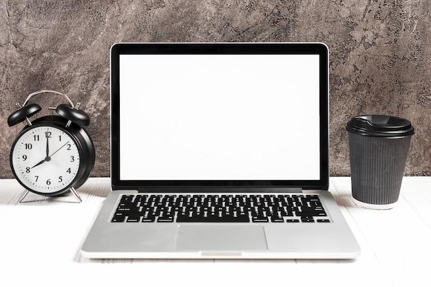 Wecker und wegwerfkaffeetasse mit einem offenen laptop auf weißem schreibtisch