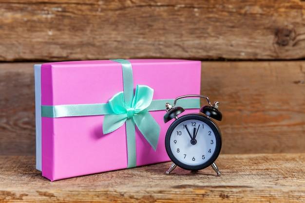 Wecker und weihnachts- oder neujahrsgeschenkbox auf altem hölzernem hintergrund