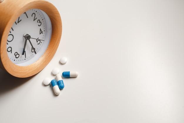 Wecker und weiße pillen auf weißem tisch