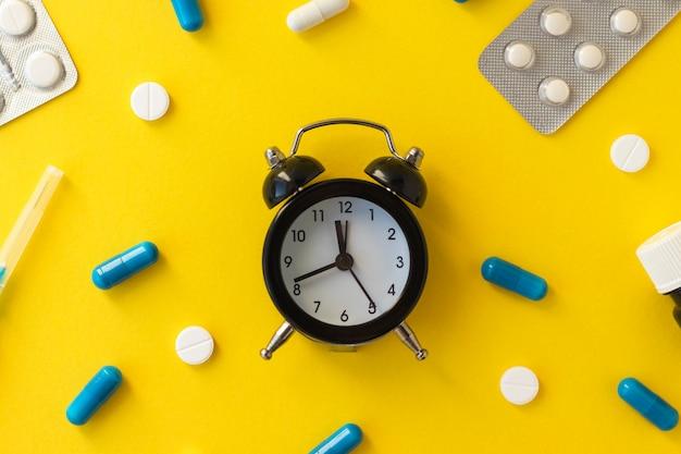 Wecker, weiße pillen, blaue kapseln, spritzennadel und flasche auf gelbem hintergrund.