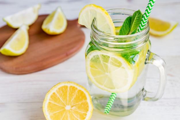 Weckglasglas selbst gemachte limonade mit zitronen, minze und grünbuchstroh auf hölzernem rustikalem hintergrund. erfrischendes sommergetränk.