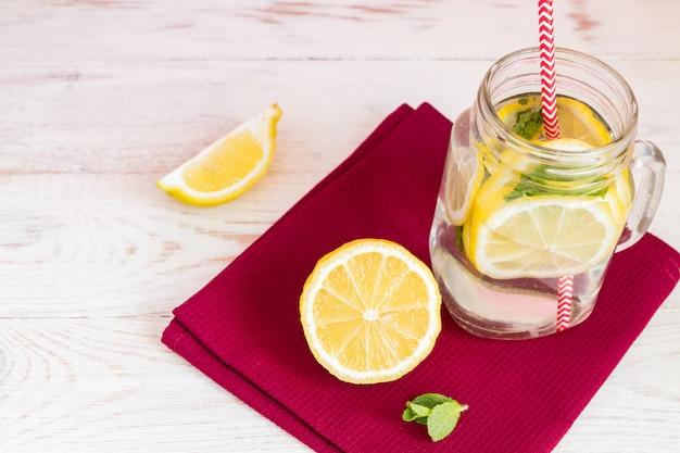 Weckglasglas selbst gemachte limonade mit zitronen, minze und rotem papierstroh auf coth serviette und hölzernem hintergrund. erfrischendes sommergetränk.