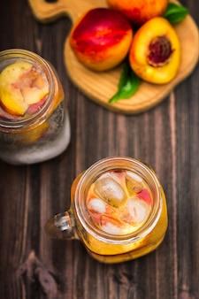 Weckglasglas selbst gemachtes pfirsicheiswasser auf einem rustikalen hölzernen hintergrund.
