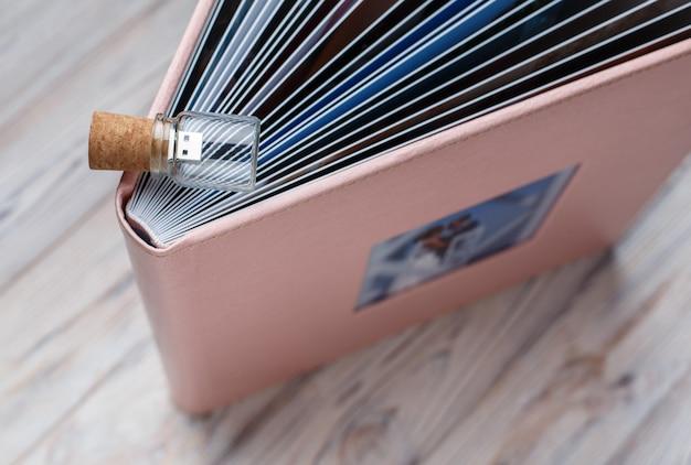 Weddind oder familienfotoalbum auf holz. fotobuch und flash-laufwerk aus der nähe. rosa fotoalbum in einem lederbezug und mit schild. leder fotobuch mit kopierraum für text
