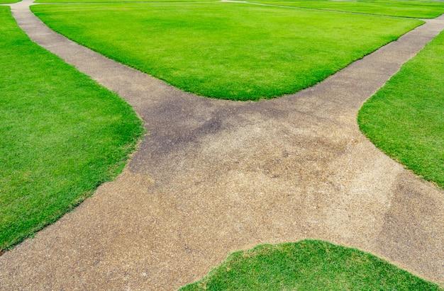 Weg auf dem grünen rasentexturhintergrund. kreuzungsweg