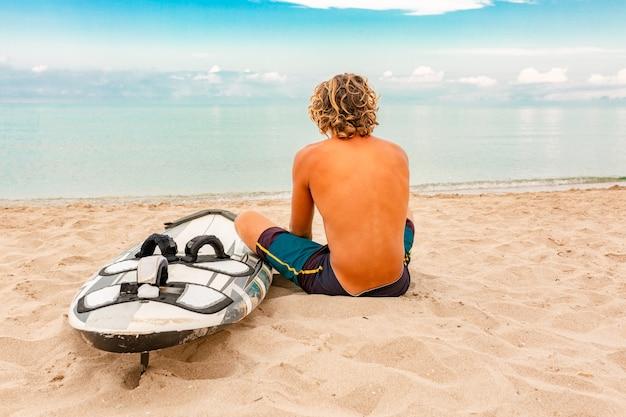 Weg des gutaussehenden mannes mit weißem leerem surfbrett warten auf welle, um stelle am seeozeanufer zu surfen. konzept von sport, fitness, freiheit, glück, neues modernes leben, hipster.