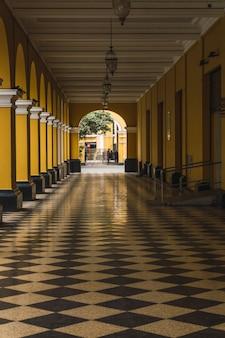 Weg mit schwarzen und weißen fliesen mit gelben säulen an der seite der passage santa rosa im historischen zentrum von lima peru