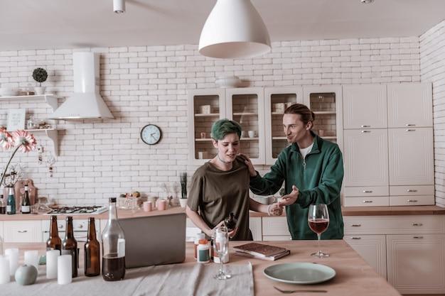 Weg von alkohol. liebevoller ehemann, der ein grünes hemd trägt und ihre frau mit alkohol vom tisch stößt