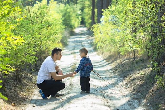 Weg zum leben. hände. die hände des vaters und seines sohnes. vater führen sohn über sommer natur im freien. männliche und kinderhände schließen sich. familie, vertrauen, schutz, fürsorge, erziehungskonzept.