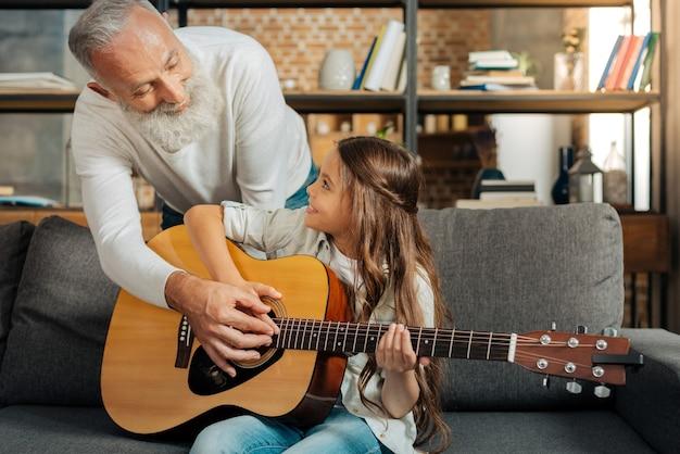 Weg zum traum. entzückendes kleines mädchen, das lernt, wie man eine gitarre spielt, während ihr geliebter großvater sie zeigt, um akkorde auf gitarre zu klimpern