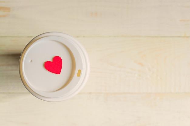 Wegwerfhandwerkspapierkaffeetasse und rotes hölzernes herz auf einer kappe. coff, zum auf holztisch zu gehen