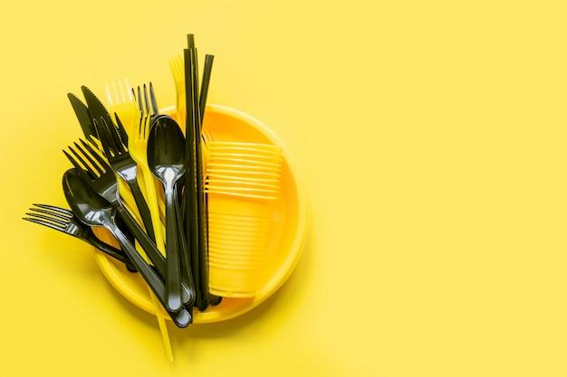 Wegwerfpicknickschwarzgeschirr auf gelb.