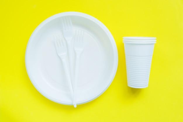 Wegwerfplastikgeschirr auf heller gelber oberfläche