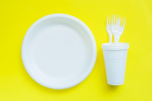 Wegwerfplastikgeschirr auf heller gelber tabelle mit kopienraum.