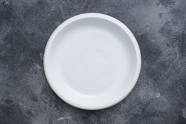 Wegwerfplastikgeschirrplatten auf dunkler tabelle mit kopienraum.