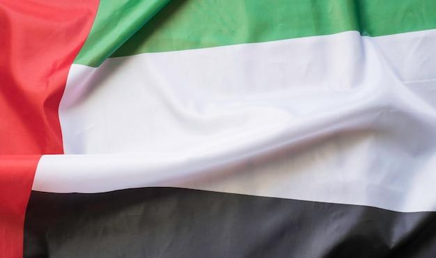 Wehende stofftextur der flagge mit farbe der vereinigten arabischen emirate, echte texturflagge der vereinigten arabischen emirate