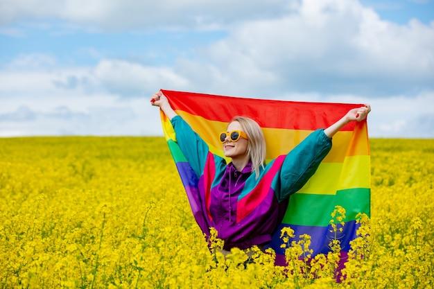 Weibchen mit lgbt-regenbogenflagge auf gelbem rapsfeld im frühjahr