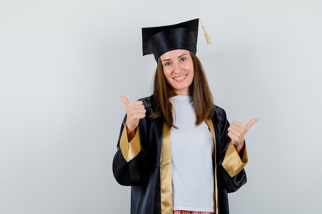 Weibliche absolventin zeigt doppelte daumen hoch im kleid, freizeitkleidung und sieht glücklich aus. vorderansicht.