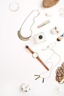Weibliche accessoires schuhe, uhren, parfüm, lippenstift, armband, halskette auf weißem hintergrund. ansicht von oben.