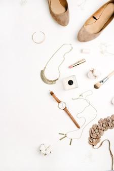 Weibliche accessoires schuhe, uhren, parfüm, lippenstift, armband, halskette mit baumwollzweig auf weißem hintergrund. ansicht von oben.