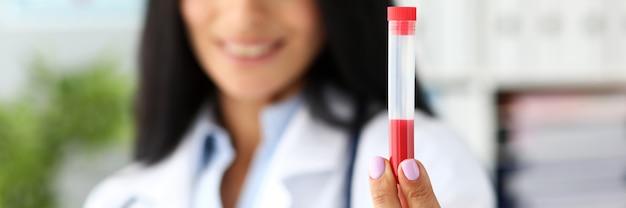 Weibliche ärztin, die kunststoff-reagenzglas hält, das rote flüssigkeit enthält