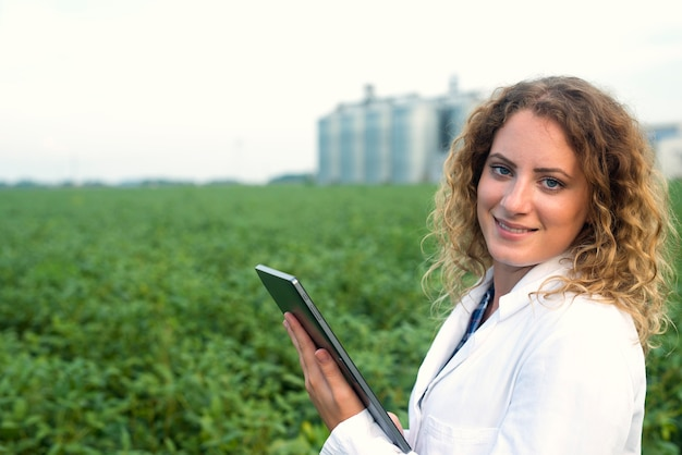 Weibliche agronomin mit tablette auf feld