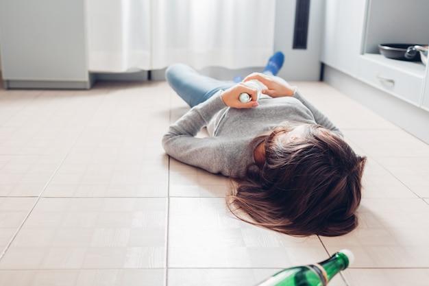 Weibliche alkoholabhängigkeit. junge frau, die auf küchenboden nach der partei hält flasche schläft