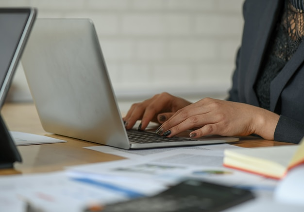 Weibliche angestellte benutzen einen laptop auf dem schreibtisch im büro.