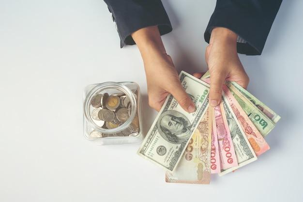 Weibliche angestellte, die geld auf einem weißen schreibtisch zählen