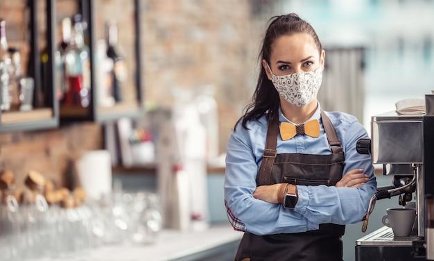 Weibliche angestellte in einem café steht unglücklich mit verschränkten armen und trägt eine gesichtsmaske.