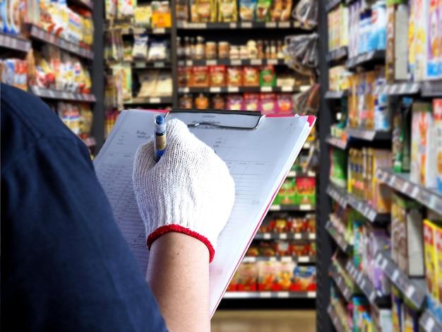 Weibliche angestelltkontrollprodukte in den regalen im supermarkt.