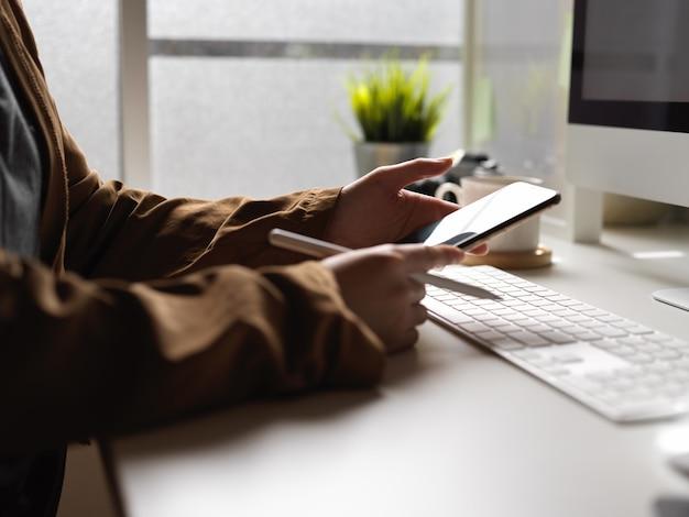 Weibliche arbeit mit computergerät beim suchen von informationen auf smartphone auf weißem schreibtisch