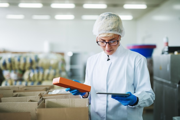 Weibliche arbeiterin, die eine schachtel mit keksen hält und tablette zur kontrolle des lagerbestands beim stehen in der lebensmittelfabrik verwendet.