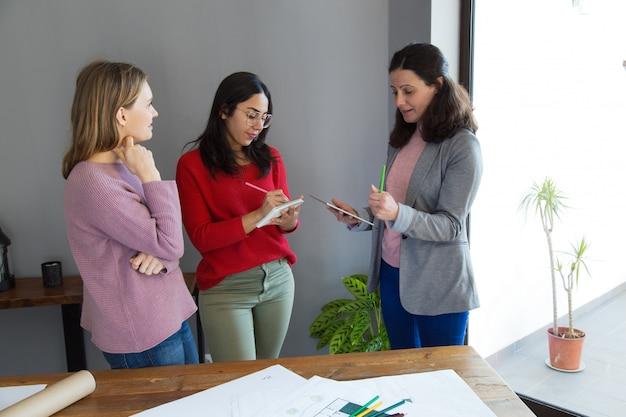 Weibliche architekten, die fragen bearbeiten und besprechen