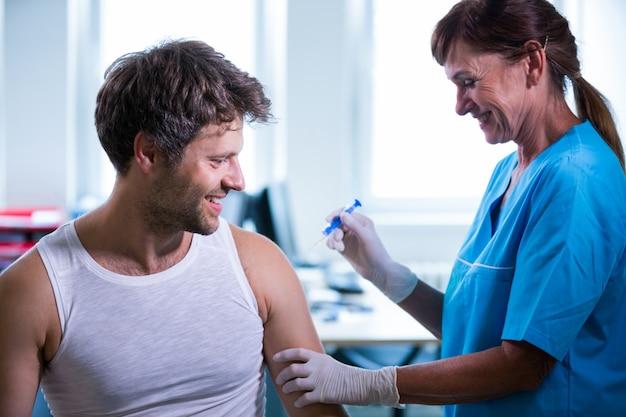 Weibliche arzt eine injektion an einen patienten geben