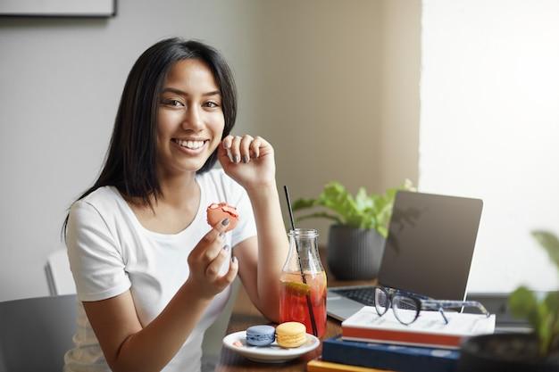 Weibliche asiatische studentin, die macaron-kuchen isst und limonade trinkt, während sie an ihrem diplom mit büchern um sie herum arbeitet.