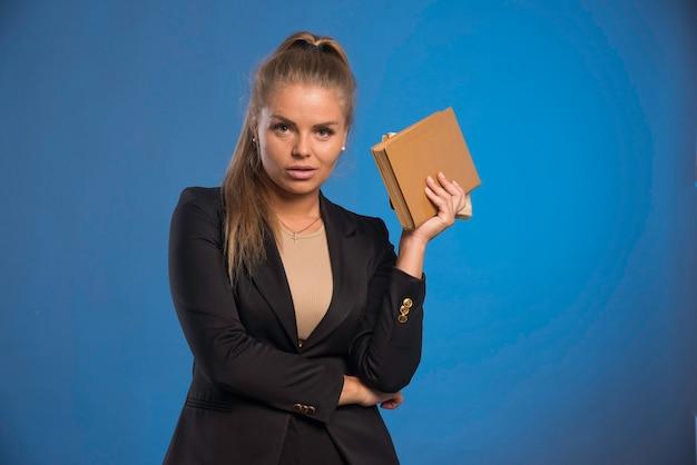 Weibliche assistentin hält ein notizbuch mit lederbezug und sieht professionell aus.