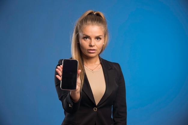 Weibliche assistentin zeigt telefonbesprechungszeit.
