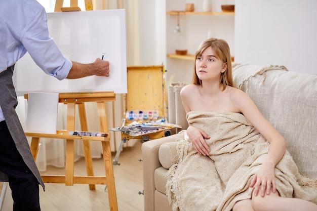 Weibliche aufstellung für porträt, professioneller maler, der porträt der jungen dame im studio zeichnet