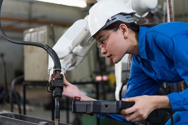 Weibliche automatisierungsingenieurin trägt eine blaue uniform mit helmsicherheitsinspektion steuert eine roboterarmschweißmaschine mit einem remote-system in einer industriefabrik. konzept der künstlichen intelligenz.