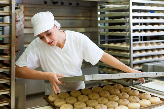 Weibliche bäcker backen brötchen