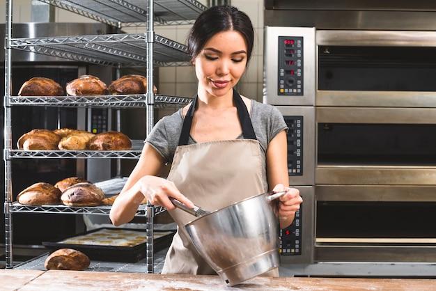Weibliche bäckerarbeitskraft, die den teig in rührschüssel an der bäckerei zubereitet