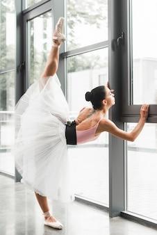 Weibliche ballerina, die ihr bein nahe dem fenster ausdehnt