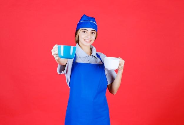 Weibliche barista, die blaue und weiße große tassen hält und dem kunden eine gibt