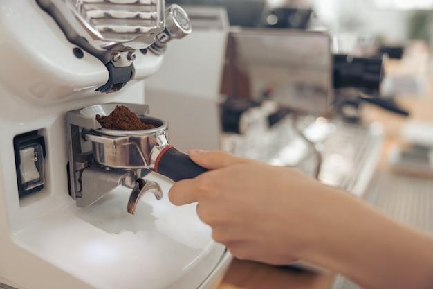 Weibliche barista-hand mit professioneller kaffeemaschine in der cafeteria