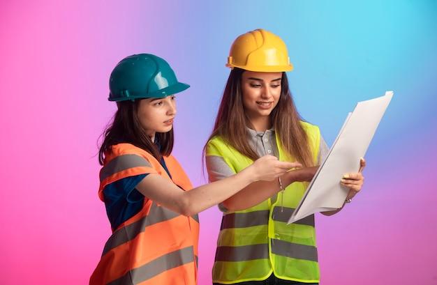 Weibliche bauingenieure arbeiten zusammen und diskutieren den projektplan auf buntem hintergrund.